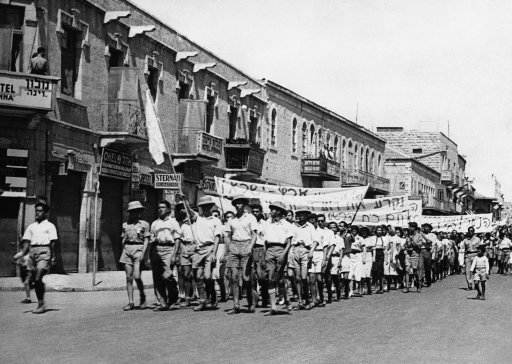 Great civil disturbances, eventually quelled by police and troops, developed from the Jewish demonstration against the British plan for the future of Palestine. In Jerusalem and other cities of Palestine, one constable was killed. Jewish youths leading the parade from which the trouble began. The Jewish flag they carry in Jerusalem, Israel on May 18, 1939. (AP Photo)