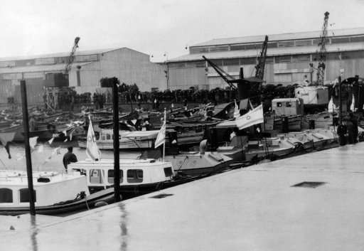 "The lighter basin, with two big goods sheds in the background, at Tel Aviv, which took its place alongside the great port cities of the world when the high commissioner for Palestine, Sir Arthur Grenfell Wauchope, declared the ""baby"" port open for passenger traffic, during the ceremony, much of which had to be curtailed owing to heavy rain, a crowd with hoisted umbrellas can be seen in rear of the picture on Feb. 23, 1938."