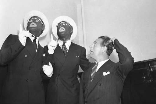 "Among the stars of stage, screen and radio who appeared in New York's Madison Square Garden in a benefit performance for the relief of persecuted European Jews who wish to settle in Palestine, were Eddie Cantor, left, George Jessel, in blackface makeup, Nov. 17, 1938. They are joined by New York Yankees ""Ironman"" Lou Gehrig, who scratches his head."