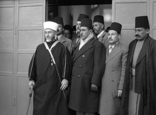The Mufti of Jerusalem appeared before the Royal Palestine commission on January 12 as the first spokesman for the Arab Case. For two months the Arab higher committee, headed by the Mufti, declined to co-operate with the commission. The decision to testify came after the Arab sovereigns of Iraq and Saudi Arabia and appeared to the committee to appear before the commission. The Mufti (left) leaving the offices of the commission after his testimony on Jan. 12, 1937.
