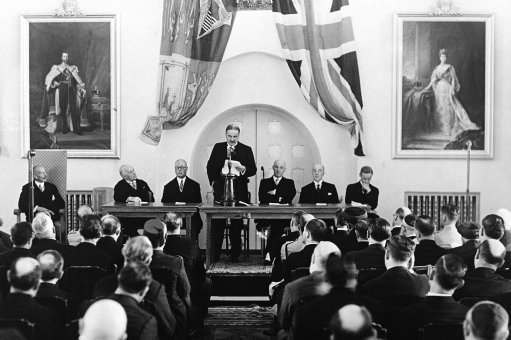 The royal commission to investigate conditions in Palestine started work at the reception held at the government house in Jerusalem, Israel on Nov. 12, 1936. Lord Peel, chairman of the royal commission, reading his opening speech. Sir Arthur Wauchope, high commissioner for Palestine is seen on left in armchair. The members of the commission are left to right: Sir Morris Carter, Sir Horace Rumbold, Vice-Chairman, Lord Peel, Sir Laurie Hammond, Sir Harold Morris, and Mr. Reginald.