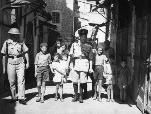 Since the British occupation of Jerusalem, Palestine, after the old city had been held for four days by Arabs, a measure of calm has descended on the district. Storm centre October 24óWhen this picture reached London by air after being was Jaffa, where there was sniping. British police captain leading Jewish kiddies to safety away from Arab snipers during the reoccupation of the old city of Jerusalem in Palestine, Israel on Oct. 24, 1938, by the British.