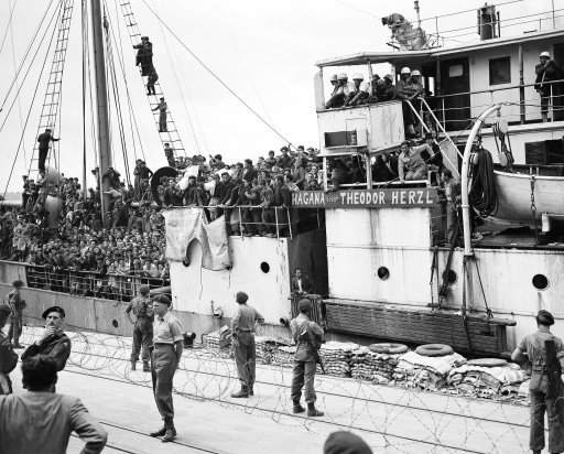 Jewish refugees, arriving on April 14, 1920 in Haifa, Palestine, aboard the Theodore Herzl. Some are carrying on their shoulders the bodies, in white shrouds, of two of their compatriots, who they say were slain when the Theodore Herzl was boarded by British personnel after unsuccessfully attempting to run the British Blockade.