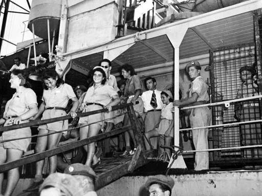 British soldier, armed with a sten gun on guard near the gangway, watches the young happy Jewish orphans as they leave the ship in the port of Haifa, Palestine, Aug. 21, 1947, where they will be bussed to Athlit for medical examination and then sent to their new homes and settlements. Five hundred orphans, the majority of whom lost their parents during World War II, were interned in Cyprus and brought to Palestine as part of the monthly immigration quota.