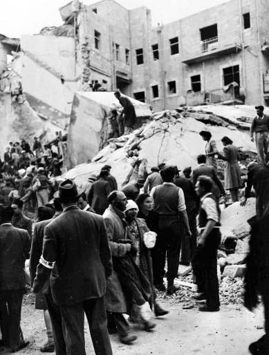 An injured Jewish couple walk past rescuers searching for wounded and dead people in the wreckage of shops on Ben Yehuda Street, Jerusalem, Feb. 22, 1948, after a bomb exploded. The bomb killed 52 Jews and wounded 100 more and levelled buildings on both sides of the street.