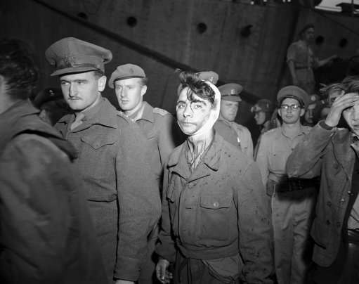 A young Jewish boy, wounded and bloody after the fight with British soldiers on board the refugee ship Knesset Israel, passes a line of soldiers to board the troopship Empire Heywood on Dec. 4, 1946 in Haifa, one of three vessels on which passengers from the refugee ship were deported.