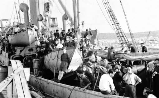 "22 ton steamer arrested off Palestine with 400 refugees aboard after a month at sea. With 401 men, women and children huddled on the upper deck with cattle and poultry. The Greek-manned panama steamer Atratto was arrested inside territorial waters off Jaffa, Palestine, on July 17, 1939. By the minesweeper H.M.S. Sutton. She was escorted into Haiffa where the captain and crew are awaiting trial for attempting to smuggle refugees into Palestine. Though crowded in misery on the open deck $25 was the cost of the passage into Palestine, the fee not including bedding or food. Associated Press Photo Shows: The crowded decks of the S.S. Atratto, showing that even the lifeboat (center) was displaced with the great crowd on the steamers' decks. These ""Berths' cost $25 a head. (AP Photo)"
