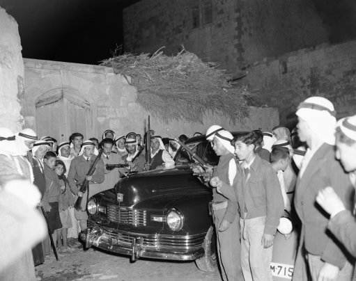 Armed Arabs surround the press car of American and British correspondents as the newsmen arrive at Taiba on a tour of Arab villages in Middle Palestine on Feb. 10, 1948. The correspondents encountered frequent roadblocks set up by the Arabs to keep a close check on traffic in fear of Jewish attacks.