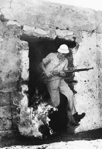 A volunteer trainee for the Hagana Leaps from a flaming house, rifle in hand on Dec. 30, 1947, during training near Tel Aviv as Jews prepare for fighting against Arabs as a result of the United Nations decision partitioning Palestine. The trainee has just set fire of the house, which formerly was an Arab home