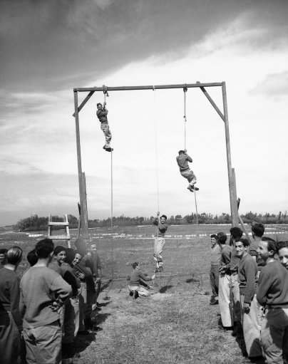 With registration on full swing, Haganah, the Jewish defense organization, puts all recruits through stiff training courses on March 11, 1948 in Jerusalem. There are several such camps, set up in secret locations. Besides training in the sued of arms, the youths are pout through a strenuous body conditioning program. At one stage of training, the recruits climb hand-over-hand up hanging ropes.