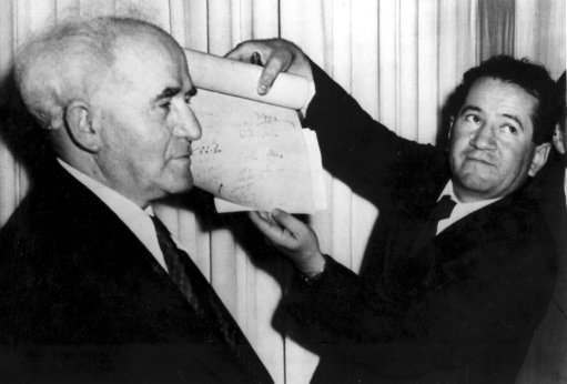 An official shows the signed document which proclaims the establishment of the new Jewish state of Israel declared by Prime Minister David Ben-Gurion, left, in Tel Aviv at midnight on May 14, 1948. The Jews declared independence in the new state of Israel as the 25-year British mandate over Palestine ends.