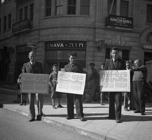 """Save our children and our parents!"" say these Jewish placards carried by men in the streets of Jerusalem, Israel on Jan. 16, 1939. ""Open the gates of Palestine to the times of Nazi prevention hatred at the Christmas period we are crying from the holy city of Jew Salem to all Christian nations to help us against ""Germany""."