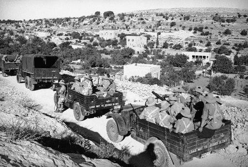 War trucks filled with fully armed British soldiers are shown on the road to ancient Hebron, city of the holy land, Israel on Sept. 5, 1938, where radial religious strife threatened to destroy the Biblical town. The town was sacked by Rebel Arabs, the driver of a British tank was slain and buildings were burned in the cut break which brought these motor lorries dashing to the terror torn city.