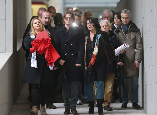 Raffaele Sollecito is flanked by his stepmother Mara Papagni, left, and his aunt Sara Achille, right, as he leaves after attending the final hearing before the third court verdict