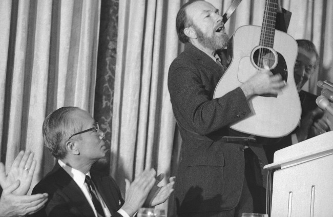 Retiring U.N. Secretary General U. Thant listening to song by folk singer Pete Seeger at luncheon honoring that at the hotel Pierre in New York on Dec. 14, 1971. (AP Photo/Marty Lederhandler)