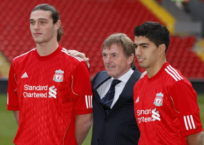 Liverpool manager Kenny Dalglish, center, poses for photos with new signings Andy Carroll, left, and Luis Suarez before a press conference at Anfield, Liverpool, England, Thursday Feb. 3, 2011.