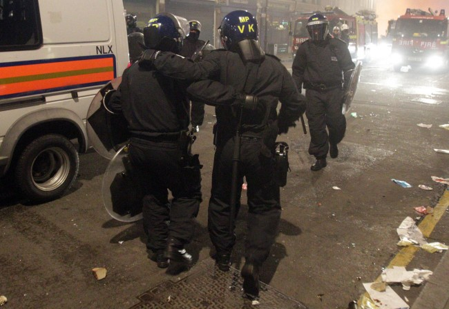 "An injured policeman is helped away from the front line by a colleague in Tottenham, north London as trouble flared after members of the community took to the streets last night to demand ""justice"", after Mark Duggan, 29, was shot dead by police on Thursday. Picture date: Sunday August 7, 2011."