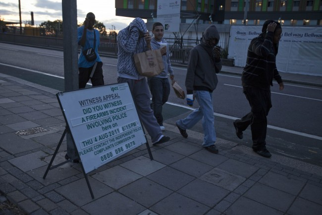 A group of youths walk past a sign where Mark Duggan, a 29-year-old father of four, was gunned down by police in disputed circumstances a week ago, Thursday, Aug. 11, 2011 in Tottenham, north London. Britain's riots began Saturday when an initially peaceful protest over a police shooting in north London turned violent. That clash triggered wider lawlessness that police struggled to halt. Across London, and then in cities throughout England, rioters set stores on fire and looted shops for sneakers, bicycles, electronics and leather goods. (AP Photo/Karel Prinsloo)
