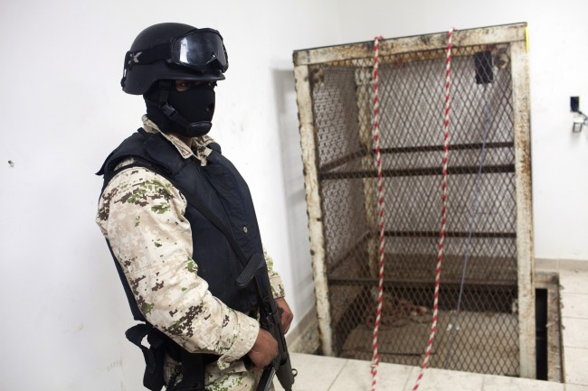 A Mexican army soldier stands next to an elevator shaft that lowers into a tunnel in the northern border city of Tijuana, Mexico Wednesday Nov. 30, 2011. U.S. authorities said they discovered a new cross-border tunnel Tuesday, the latest in a spate of secret passages found to smuggle drugs from Mexico. The tunnel was found in San Diego's Otay Mesa area, a warehouse district across the border from Tijuana, said Lauren Mack, a spokeswoman for U.S. Immigration and Customs Enforcement. (AP Photo/Alex Cossio)