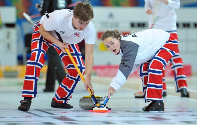 Norway's Martin Sesaker, left, and his teammate Stine Haalien work on the stone while playing against Estonia during a mixed team curling event at the first winter Youth Olympic Games in Innsbruck, Austria, Tuesday, Jan. 17, 2012. (AP Photo/Kerstin Joensson)