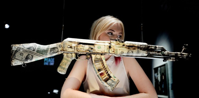 Emma Gilhooly studies the USA Dollar bill covered AK47 machine gun by Bran Symondson, at the AKA Peace one day show in which artists adapt the favourite weapon of terrorists into works of art, at the Institute of Contemporary Arts, London. Picture date: Wednesday September 26, 2012.