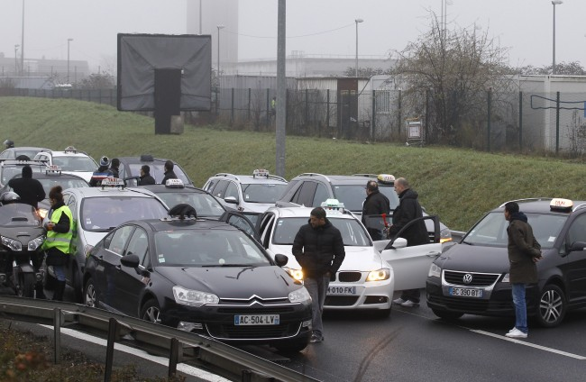Taxi drivers stop the traffic on the highway leading to Paris, Thursday, Jan. 10, 2013 at Roissy airport. Taxi drivers across France were putting on the brakes to clog traffic, slow access to airports and force would-be passengers to find alternate transport in a strike over government efforts to deregulate the transportation industry.
