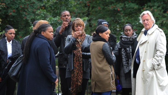 Family and friends of Mark Duggan, accompanied by Michael Mansfield QC (light coat) look on as the jury in the inquest into his death visit the scene of his shooting in Tottenham, north London. Picture date: Thursday September 19, 2013.