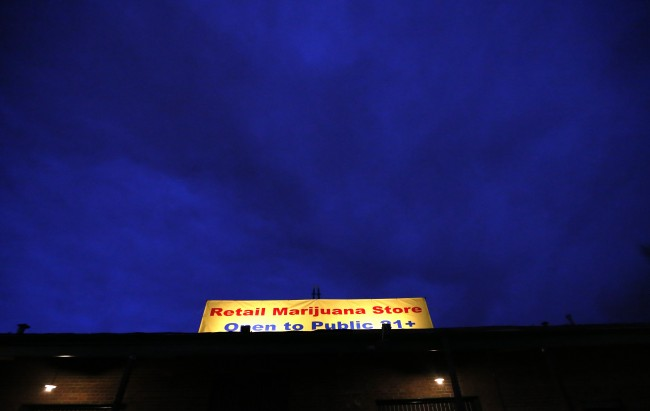 "Before dawn, a sign is illuminated at 3D Cannabis Center, which opened as a legal recreational retail outlet in Denver, early Wednesday, Jan. 1, 2014. Colorado began retail marijuana sales on Jan. 1, a day some are calling ""Green Wednesday."""