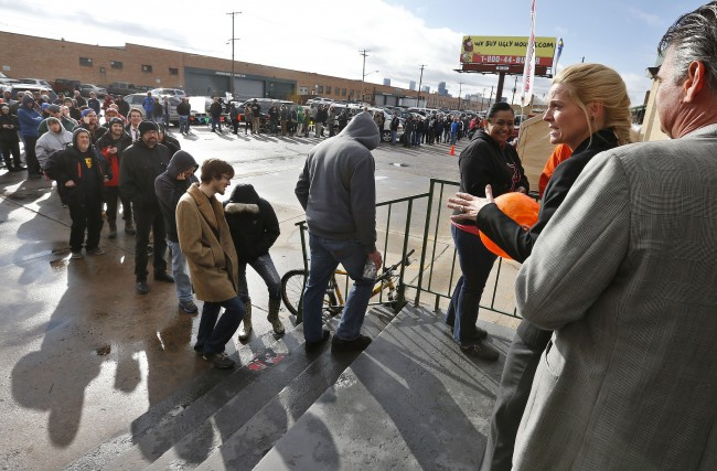 Store owner Toni Fox, second from right, greets customers standing in a snaking line numbering several hundred people shortly after the opening of her 3D Cannabis Center in Denver at 8am on Wednesday Jan. 1, 2014