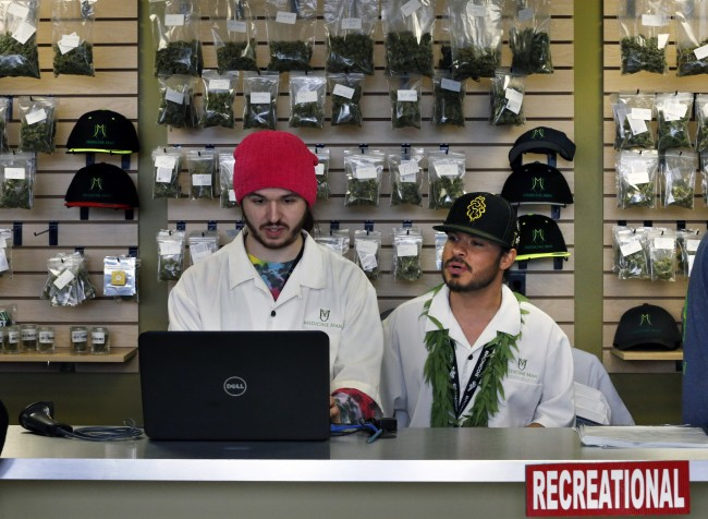 Employees David Marlow, right, and Chris Broussard work behind sales counter inside Medicine Man marijuana retail store, which opened as a legal recreational retail outlet in Denver on Wednesday Jan. 1, 2014