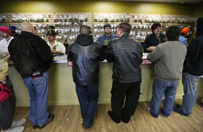 Employees help customers at the crowded sales counter inside Medicine Man marijuana retail store, which opened as a legal recreational retail outlet in Denver on Wednesday Jan. 1, 2014