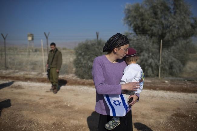 Israeli settlers gather during a visit of Israeli politicians at Gitit settlement in the West Bank's Jordan Valley, Thursday, Jan. 2, 2014.