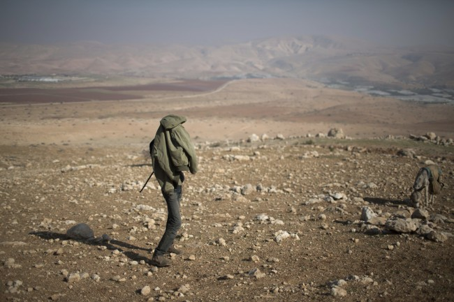 A young Palestinian shepherd lights a cigaret near the settlement of Mehola in the Jordan Valley, a strip of West Bank land along the border with Jordan, Thursday, Jan. 2, 2014.