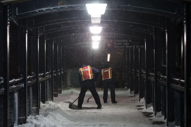 Workers clear snow from a pedestrian passageway at the Astoria Blvd. subway station, Friday, Jan. 3, 2014, in the Queens borough of New York. New York City public schools were closed Friday after up to 7 inches of snow fell by morning in the first snowstorm of the winter. (AP Photo/John Minchillo)