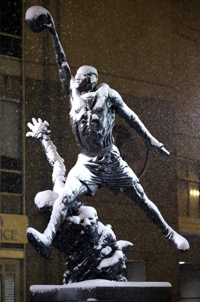 Michael Jordan statue is covered by snow outside of United Center in Chicago on Saturday, Jan. 4, 2014. The National Weather Service issued a winter storm warning that is in effect until 6 p.m. Sunday calling for moderate to heavy snow that will make for hazardous travel conditions. (AP Photo/Nam Y. Huh)