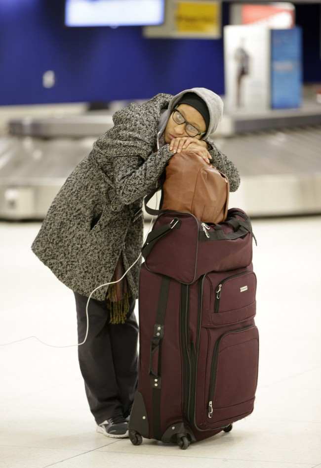 A woman rests on her luggage as she waits in the baggage area of Terminal 2 at Kennedy International Airport after a Delta flight from Toronto to New York skidded off the runway into a snow bank, temporarily halting all airport flights, Sunday, Jan. 5, 2014, in New York. (AP Photo/Kathy Willens)