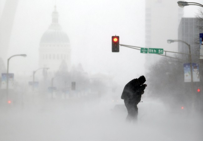 A person struggles to cross a street in blowing and falling snow Sunday, Jan. 5, 2014, in St. Louis. Snow that began in parts of Missouri Saturday night picked up intensity after dawn Sunday with several inches of snow on the ground by midmorning and more on the way. (AP Photo/Jeff Roberson)