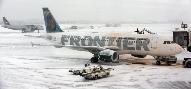 A crew works to de-ice planes at O'Hare International Airport in Chicago on Sunday, Jan. 5, 2014. In Chicago, temperatures were expected to fall throughout Sunday to about 11 degrees by 5 p.m. About 1,200 flights had been cancelled Sunday morning at O'Hare and Midway international airports in Chicago, aviation officials said. (AP Photo/Nam Y. Huh)