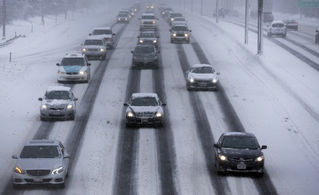 Motorists drive along a snow covered northbound Interstate-94 in Chicago on Sunday, Jan. 5, 2014. Sunday night temperatures will drastically drop to about minus 20 degrees. (AP Photo/Nam Y. Huh)