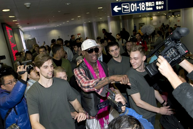 Former NBA basketball player Dennis Rodman, center, gestures to the media as he arrives at the departure hall of Beijing International Capital Airport in Beijing Monday, Jan. 6, 2014.