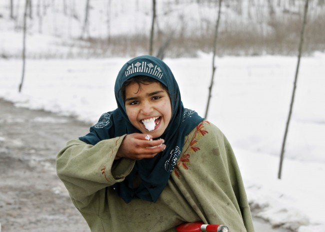 A Kashmiri Muslim girl smiles as she eats snow on the outskirts of Srinagar, India, Monday, Jan. 6, 2014. Overnight snowfall in Kashmir led to an increase in night temperatures by several notches in most places of the valley, according to local reports. (AP Photo/Mukhtar Khan)