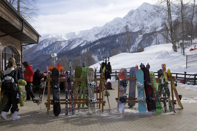 In this Wednesday, Feb. 6, 2013, file photo, snowboarders and skiers rest after competitions, in Rosa Khutor, some 60 km east of the Black Sea resort of Sochi, Russia. For visitors to the Winter Olympics, Sochi may feel like a landscape from a dream _ familiar and strange at once. Palm trees evoke a tropical seaside resort, but the Black Sea itself is seriously cold; turn away from the palms and the jagged, snow-covered peaks of the Caucasus Mountains rise nearby. (AP Photo/Ivan Sekretarev, file)