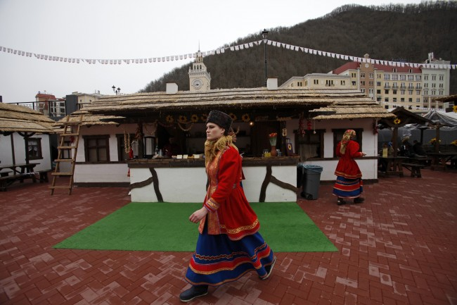 In this Feb. 22, 2013, file photo, waiters dressed in Russian Cossack costumes work at a street restran in Krasnaya Polyana, mountain Olympic cluster, 60 kilometers East from Sochi, Russia. For visitors to the Winter Olympics, Sochi may feel like a landscape from a dream _ familiar and strange at once. Palm trees evoke a tropical seaside resort, but the Black Sea itself is seriously cold; turn away from the palms and the jagged, snow-covered peaks of the Caucasus Mountains rise nearby. (AP Photo/Alexander Zemlianichenko, file)