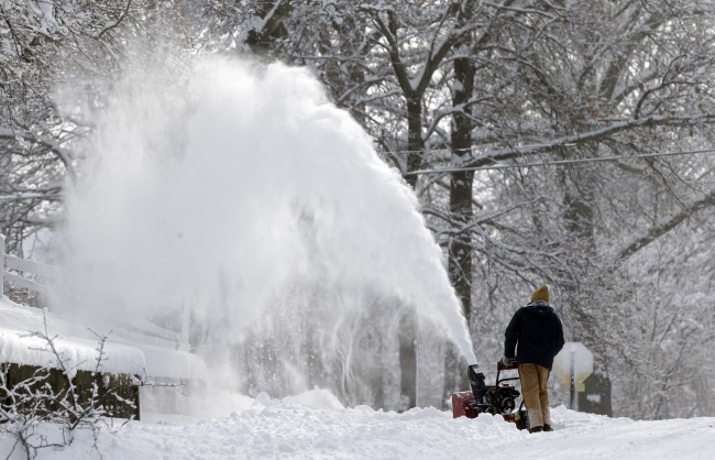 Discharge from a snow blower falls in front of snow covered tress as a man clears his driveway in Indianapolis Monday, Jan. 6, 2014 as temperatures hovered around 10 below zero. More than 12 inches of snow fell on Sunday. (AP Photo/Michael Conroy)