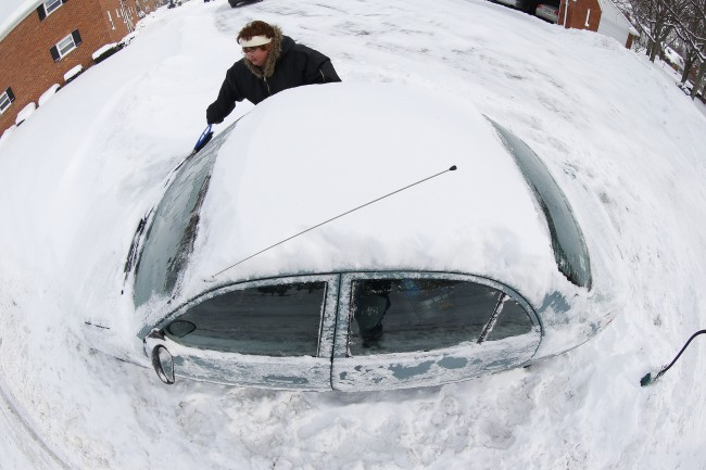 In an image made with a fisheye lens, Marguerite Johnston uncovers her car in Grosse Pointe, Mich., Monday, Jan. 6, 2014. Michigan residents are preparing for diving temperatures as they dig out from more than 15 inches of snow in places. (AP Photo/Paul Sancya)