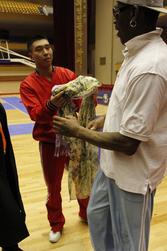 A North Korean basketball player returns the scarf that Dennis Rodman was wearing and took off during a practice between North Korean and US basketball players in Pyongyang, North Korea on Tuesday, Jan. 7, 2014.