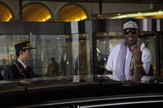 Dennis Rodman greets the media as he waits to get inside a car outside a Pyongyang hotel