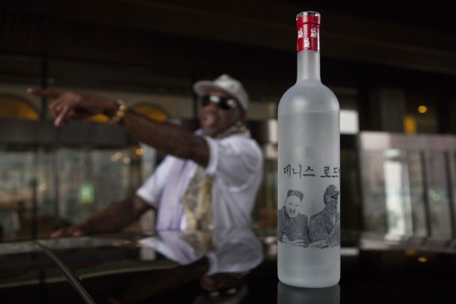 Dennis Rodman reaches to take a bottle of vodka from his bodyguard outside a Pyongyang hotel on Tuesday, Jan. 7, 2014. The bottle's handmade illustration, showing Rodman with North Korean leader Kim Jong Un and Rodman's name in Korean, was designed locally.