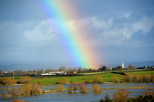 A rainbow over flood water which covers part of the Somerset Levels in Somerset, as around 100 flood warnings in England, along with four in Scotland and one in Wales remain in place with forecasters predicting freezing temperatures and possibly snow in the north.