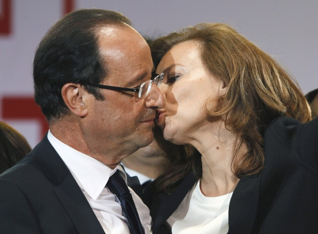This Sunday, May 6, 2012, file photo shows French president-elect Francois Hollande kissing his companion, Valerie Trierweiler, after greeting crowds gathered to celebrate his election victory in Bastille Square in Paris. Hollande is threatening legal action over magazine report saying he is having a secret affair with a French actress. The magazine Closer published images Friday Jan.10, 2014 showing his bodyguard and a helmeted man it says is Hollande visiting what it says is the apartment of the actress. (AP Photo/Francois Mori, File)